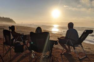Freunde sitzen zusammen und beobachten den Sonnenuntergang